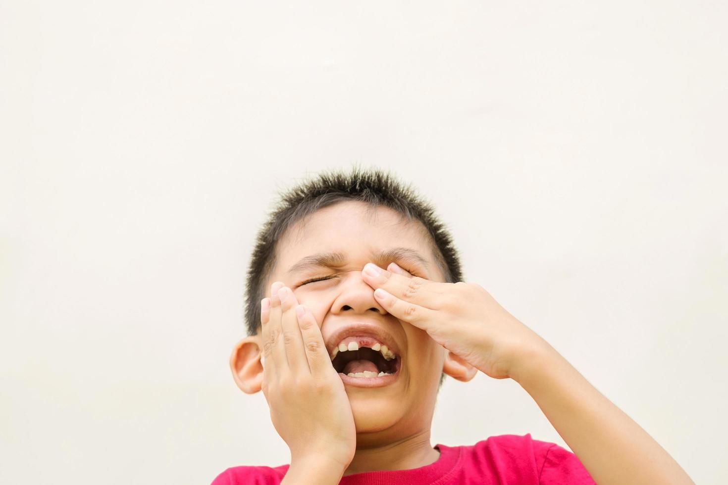 niño pequeño sosteniendo su cabeza con dolor de muelas foto