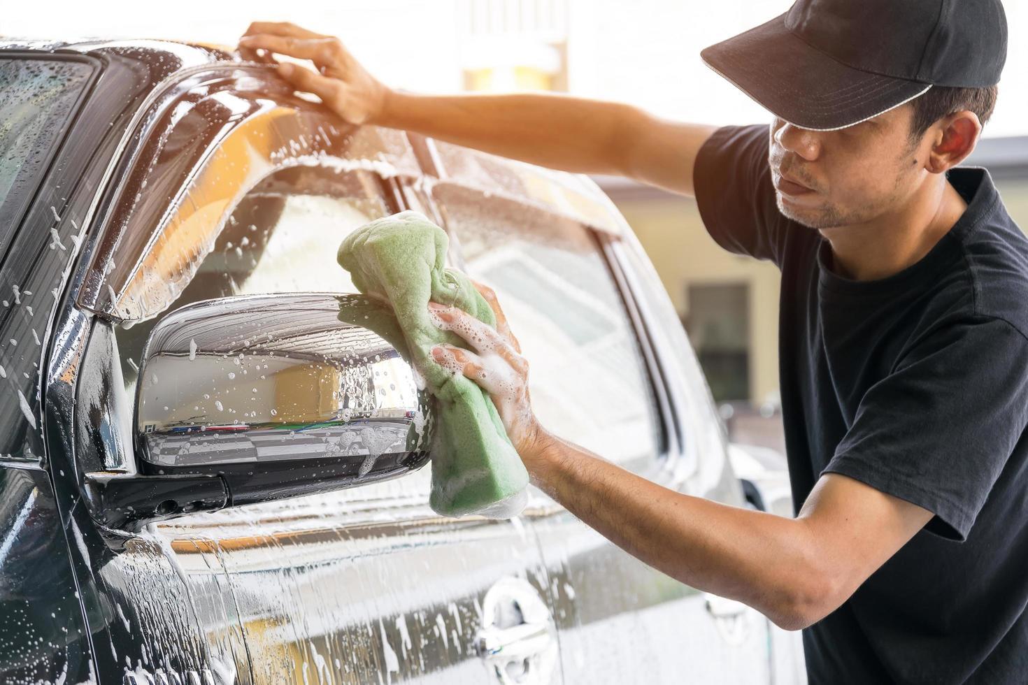 hombre lavando un auto en el lavado de autos foto