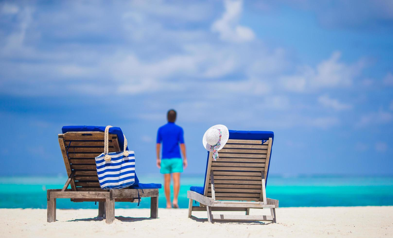 Lounge chairs on a beach with a person in the distance photo