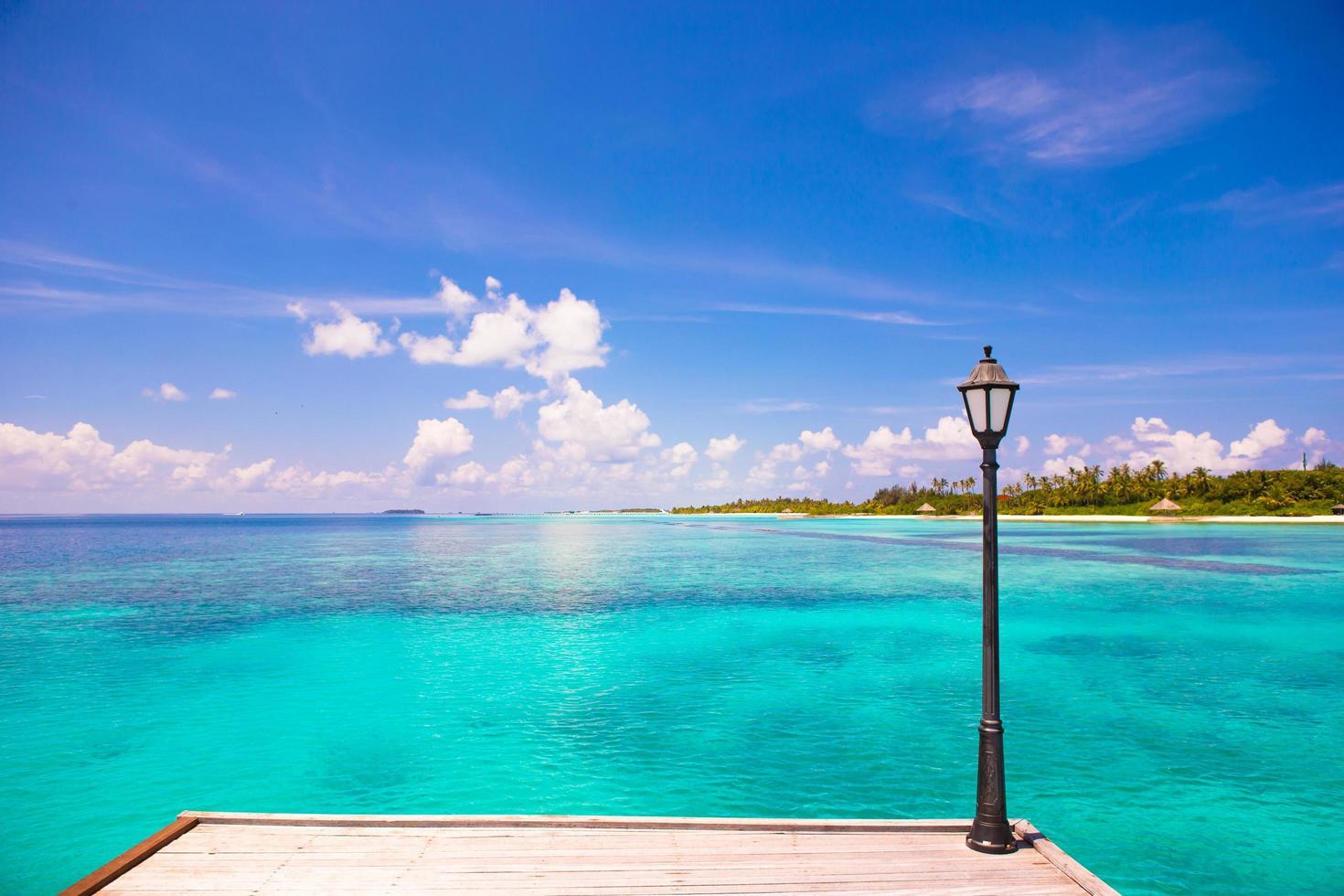 Muelle con poste de luz junto a una playa tropical. foto