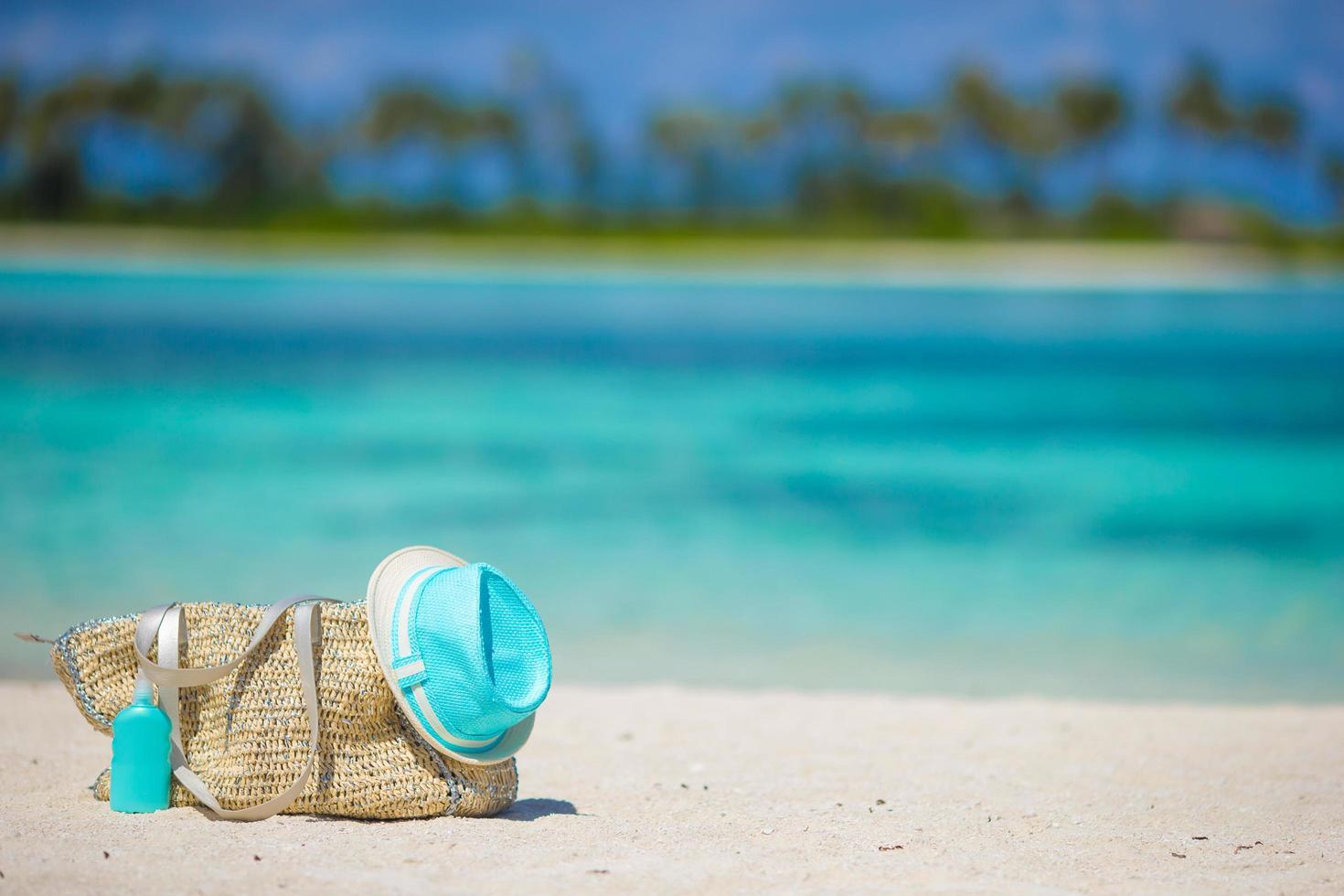 Bolsa de mimbre con sombrero y protector solar en la playa foto