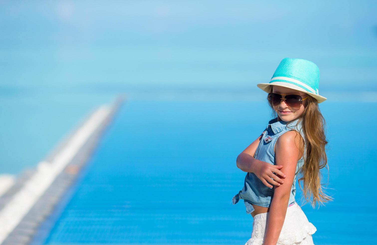 Girl in a hat at a beach photo