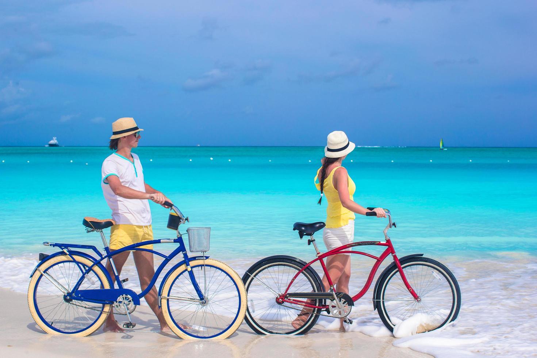Couple with bikes on a white sandy beach photo