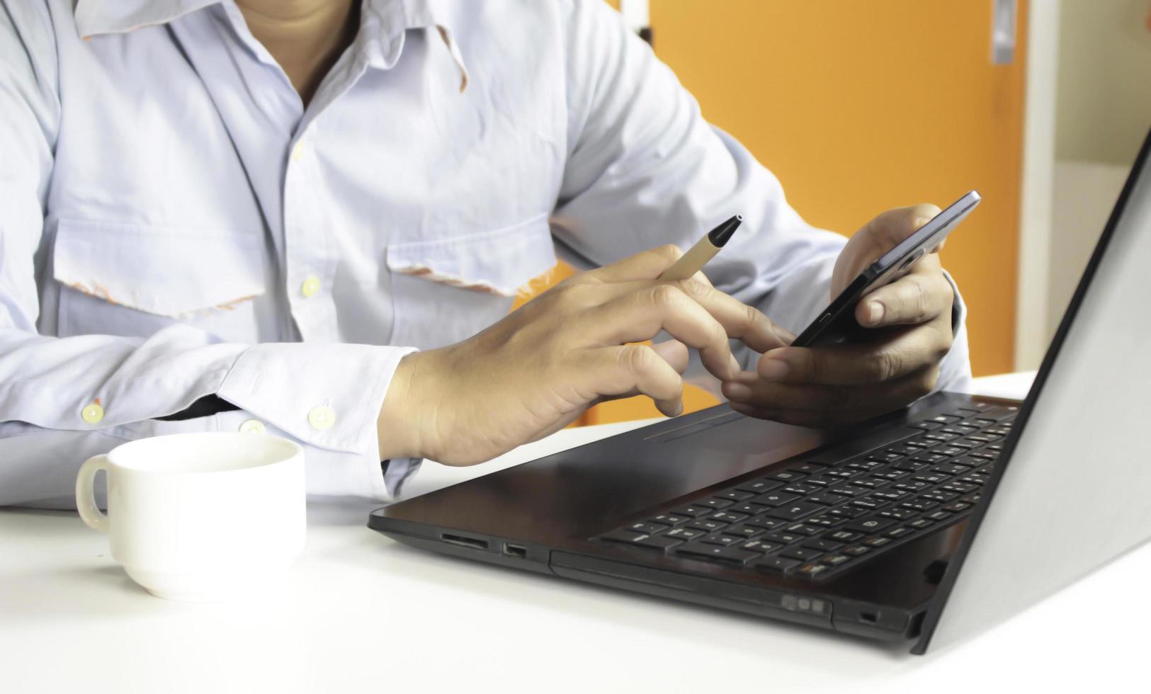 persona que usa una computadora portátil y un teléfono inteligente para comprar en línea foto