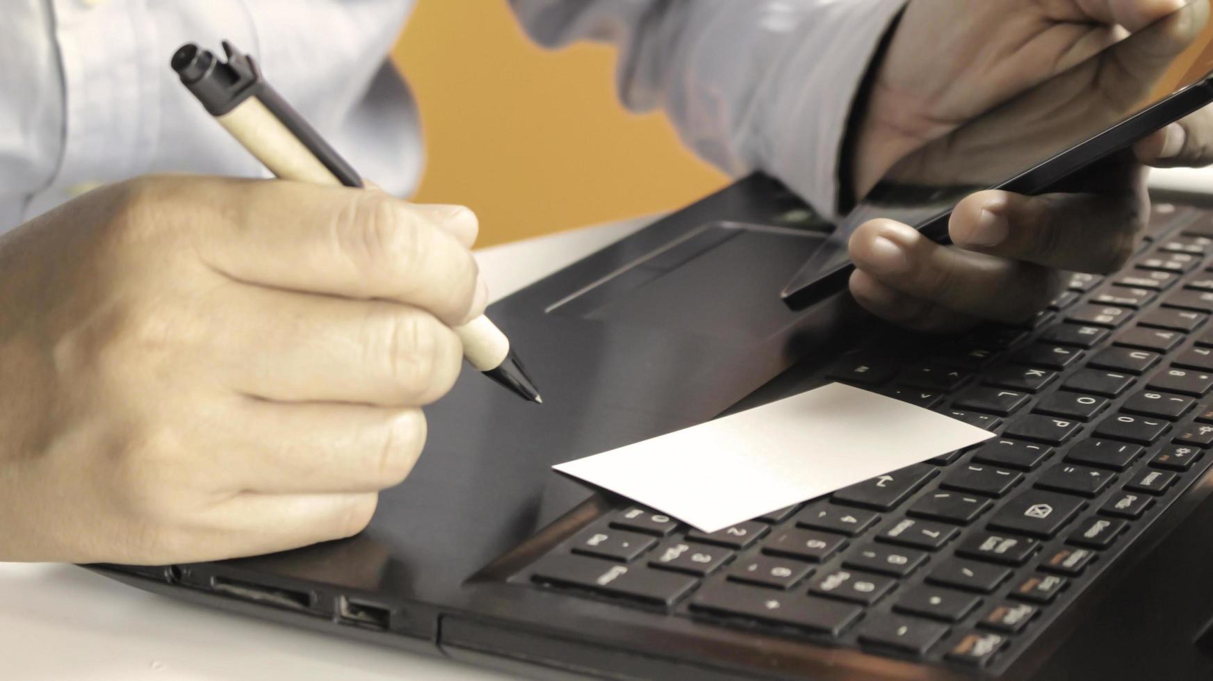 manos usando laptop y smartphone foto