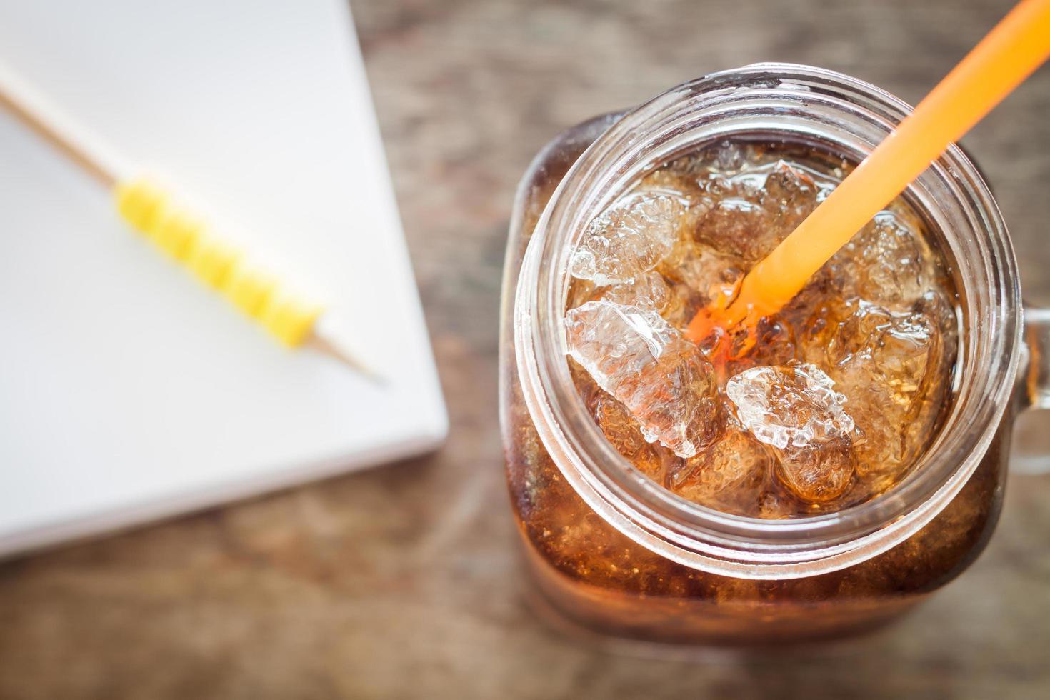 Vaso de cola con hielo sobre una mesa de madera foto