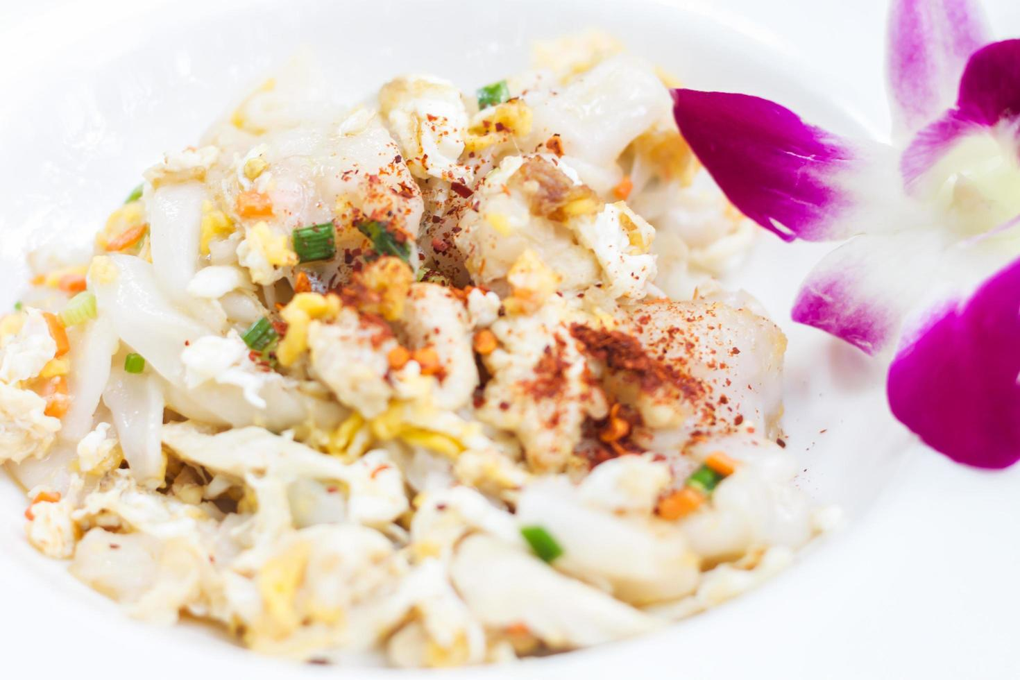 Close-up of fried noodles with pork and a flower photo