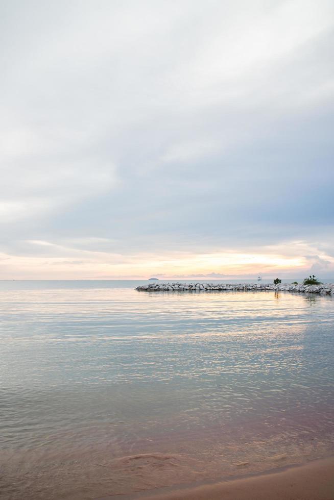 sol naciente en la orilla del mar foto