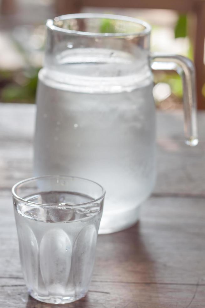jarra de vidrio de agua fría con taza foto