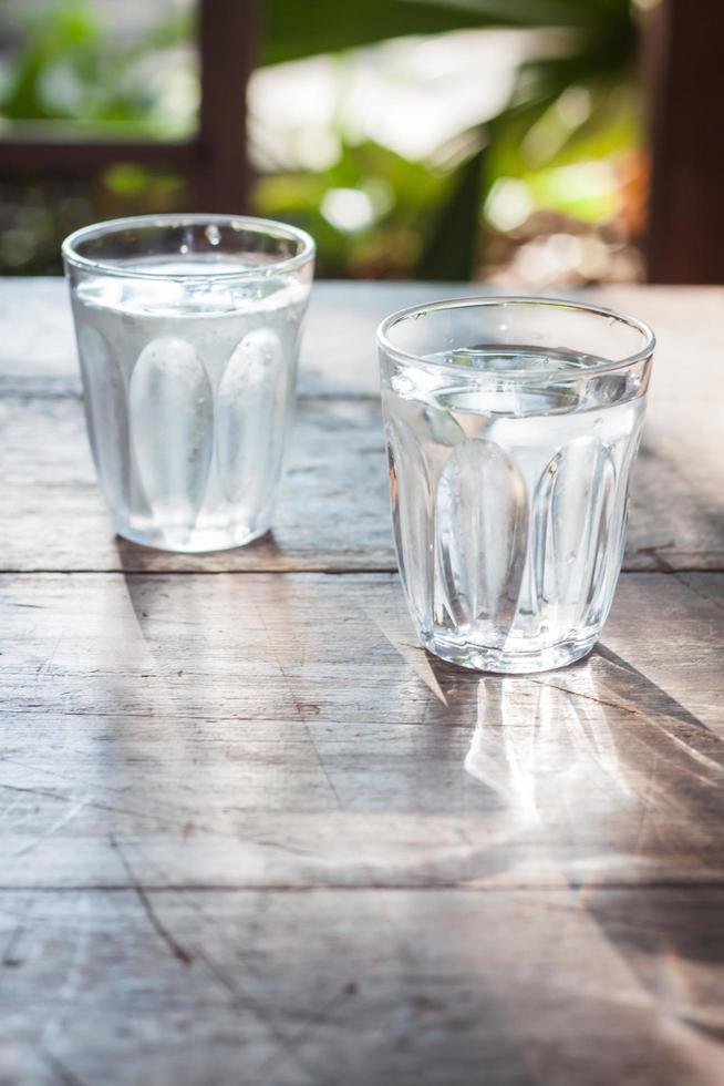 vasos de agua fría en una mesa de madera foto