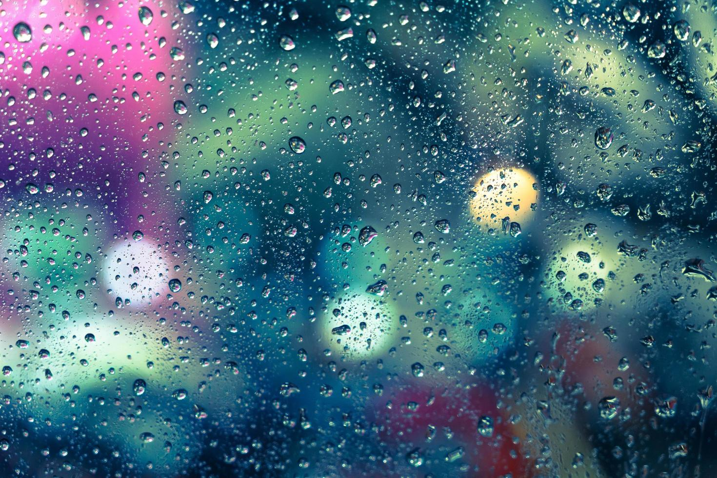 Rain drops on the window with colorful bokeh photo
