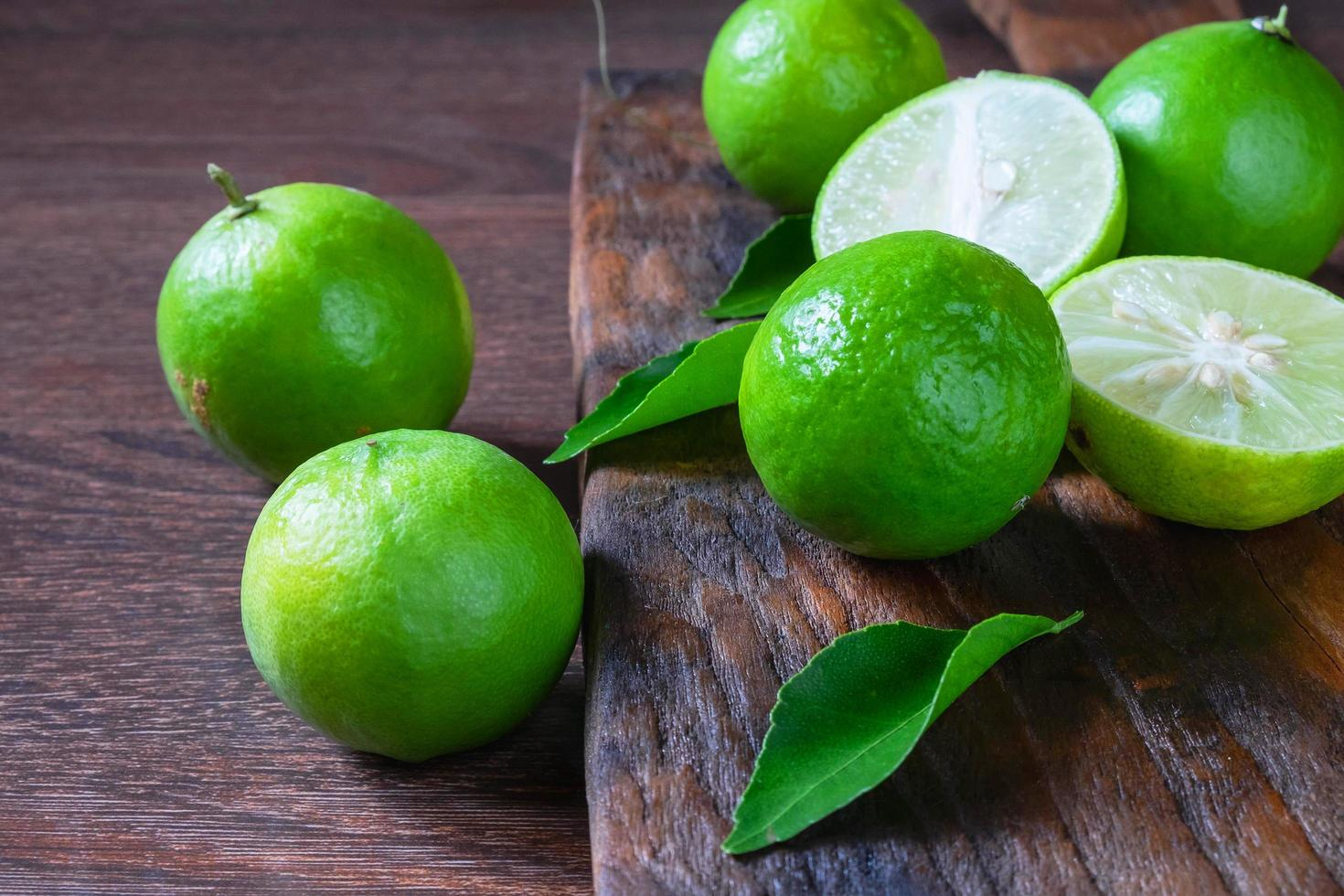 Fresh ripe limes on a wooden background photo