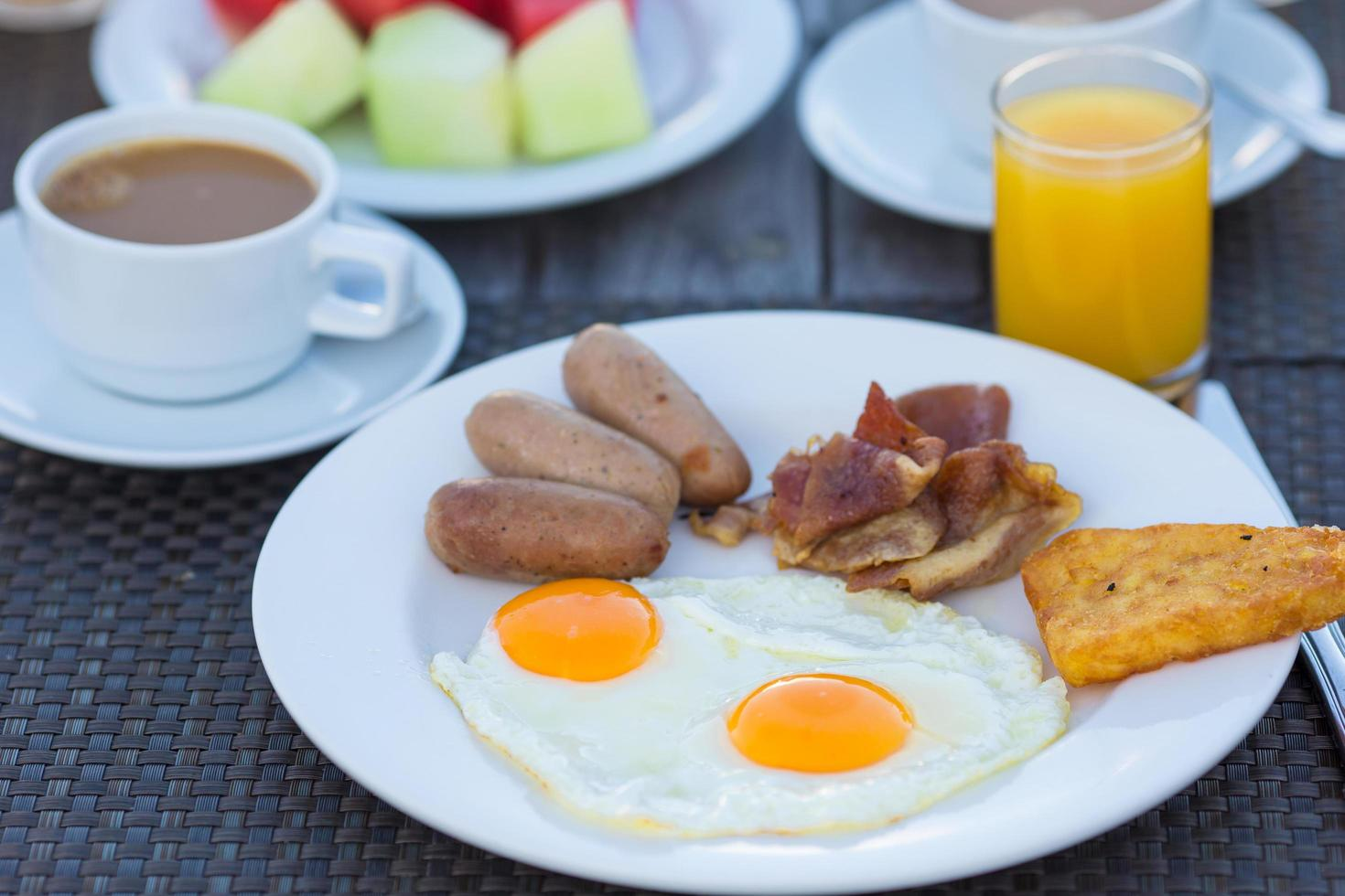 Plate with fried eggs, bacon and sausages photo