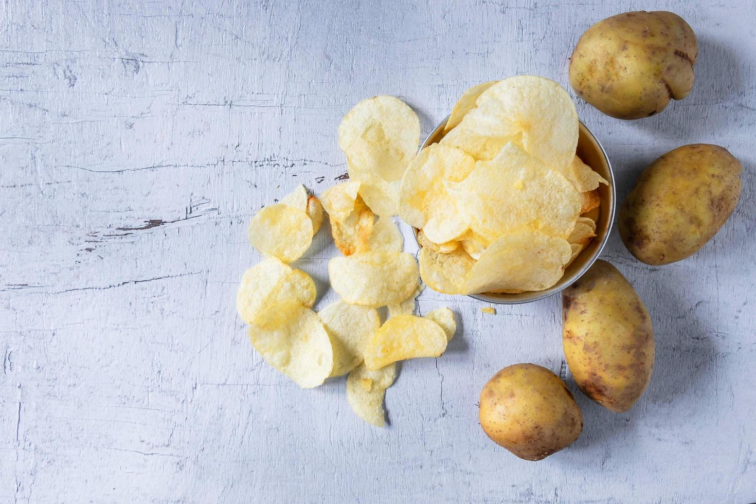 Fried potato chips and raw potato in a bowl photo