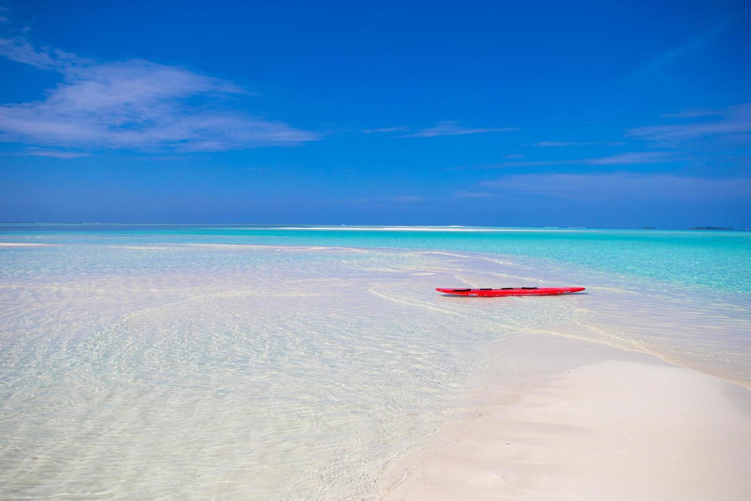 Tabla de surf roja en la playa de arena blanca foto
