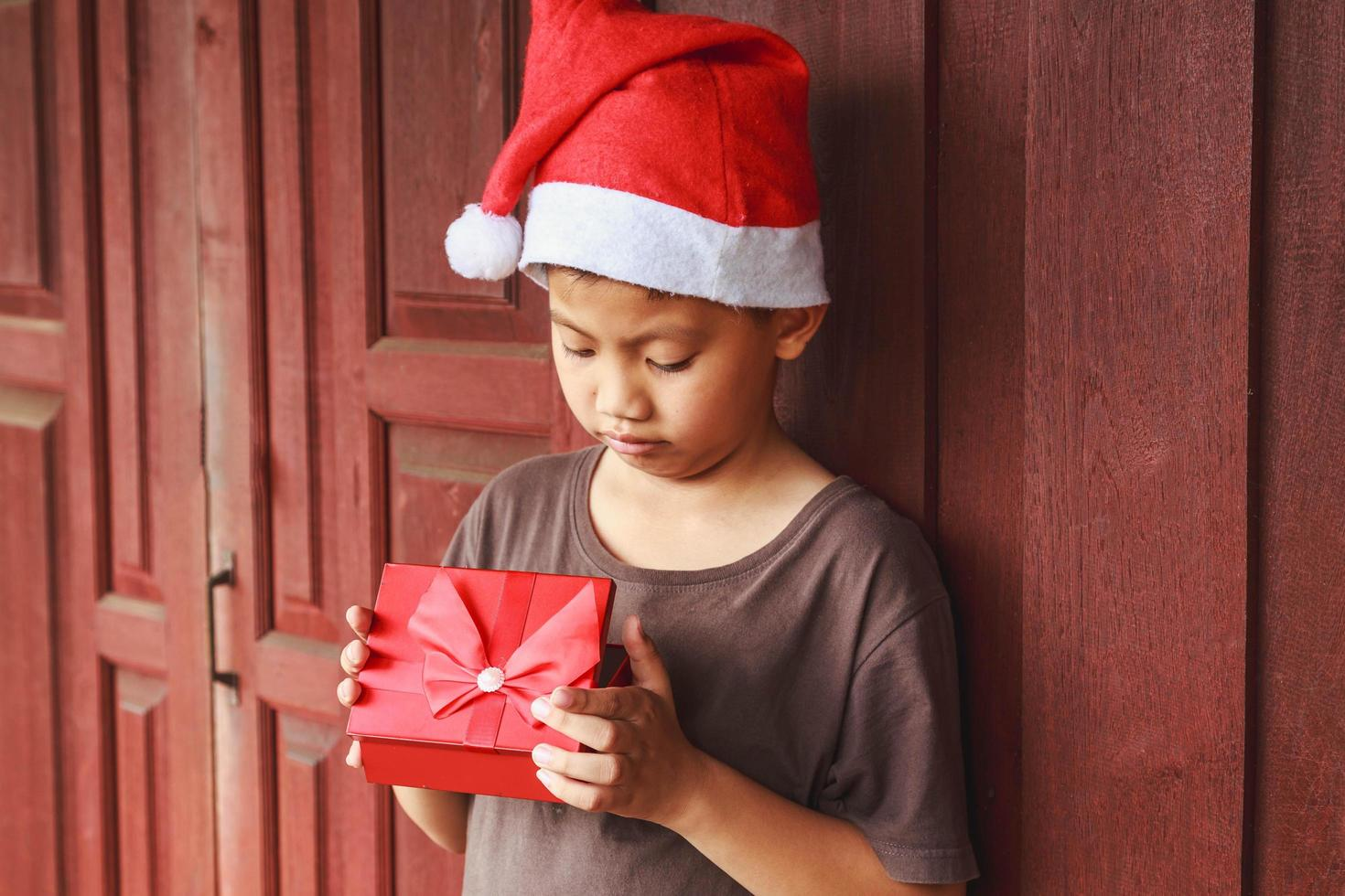 niño con caja de regalo el día de navidad foto