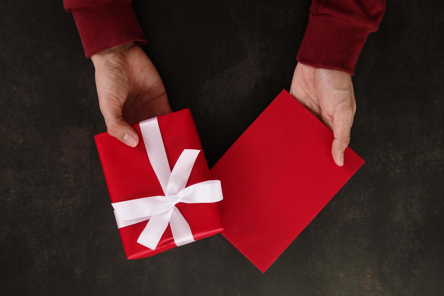 Hands holding red greeting card mockup photo