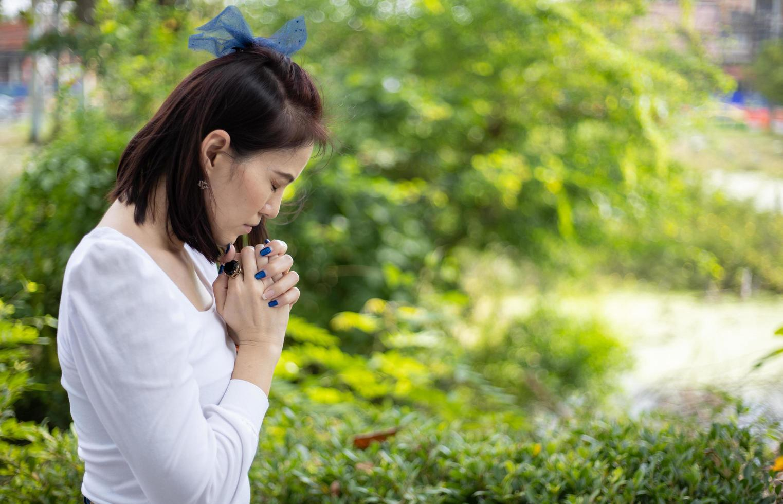 Una mujer con un vestido blanco rezando en el jardín bajo la luz del sol foto