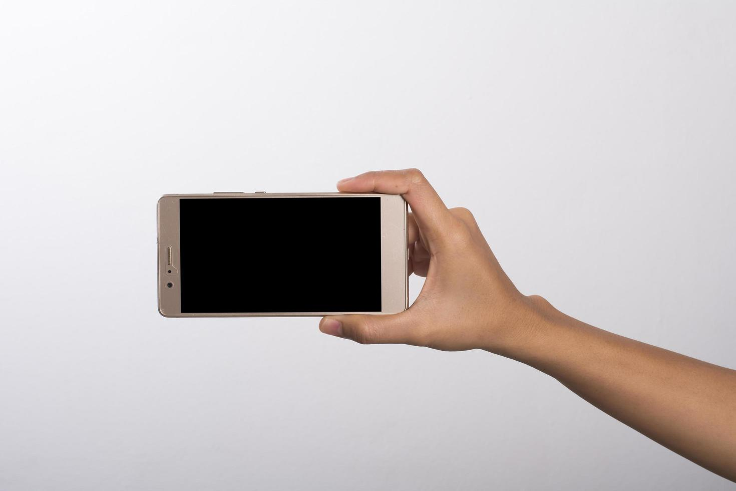 Close-up of woman's hand on mobile phone isolated on white background photo