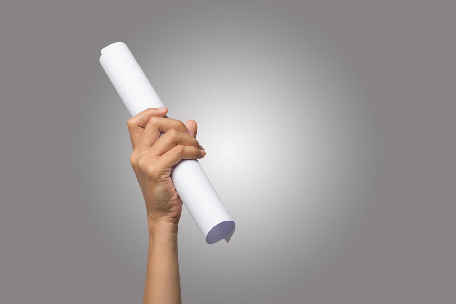 Close-up de una mano sujetando el rollo de papel aislado sobre fondo neutro foto