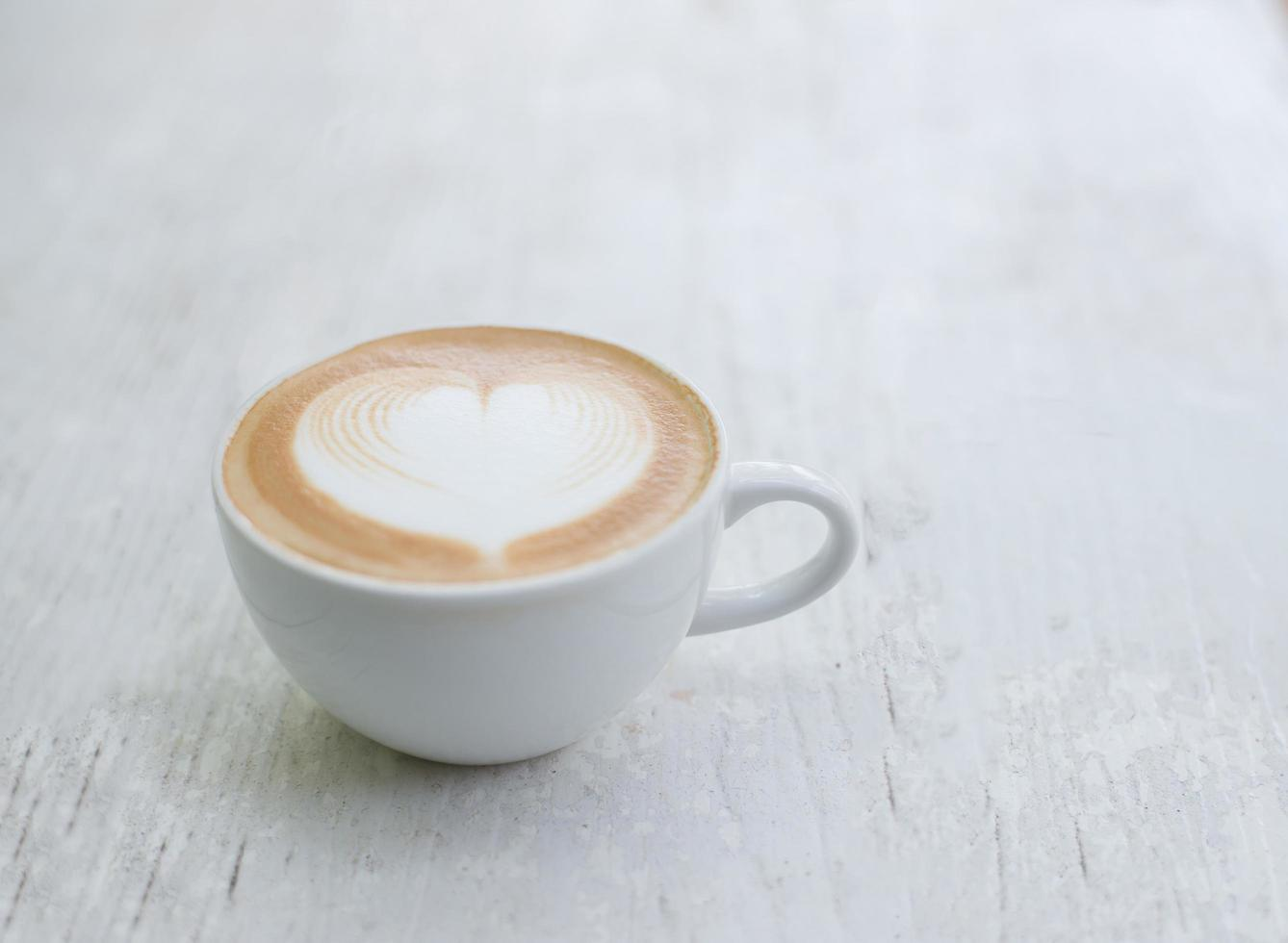 Cup of latte with heart shape on white table photo