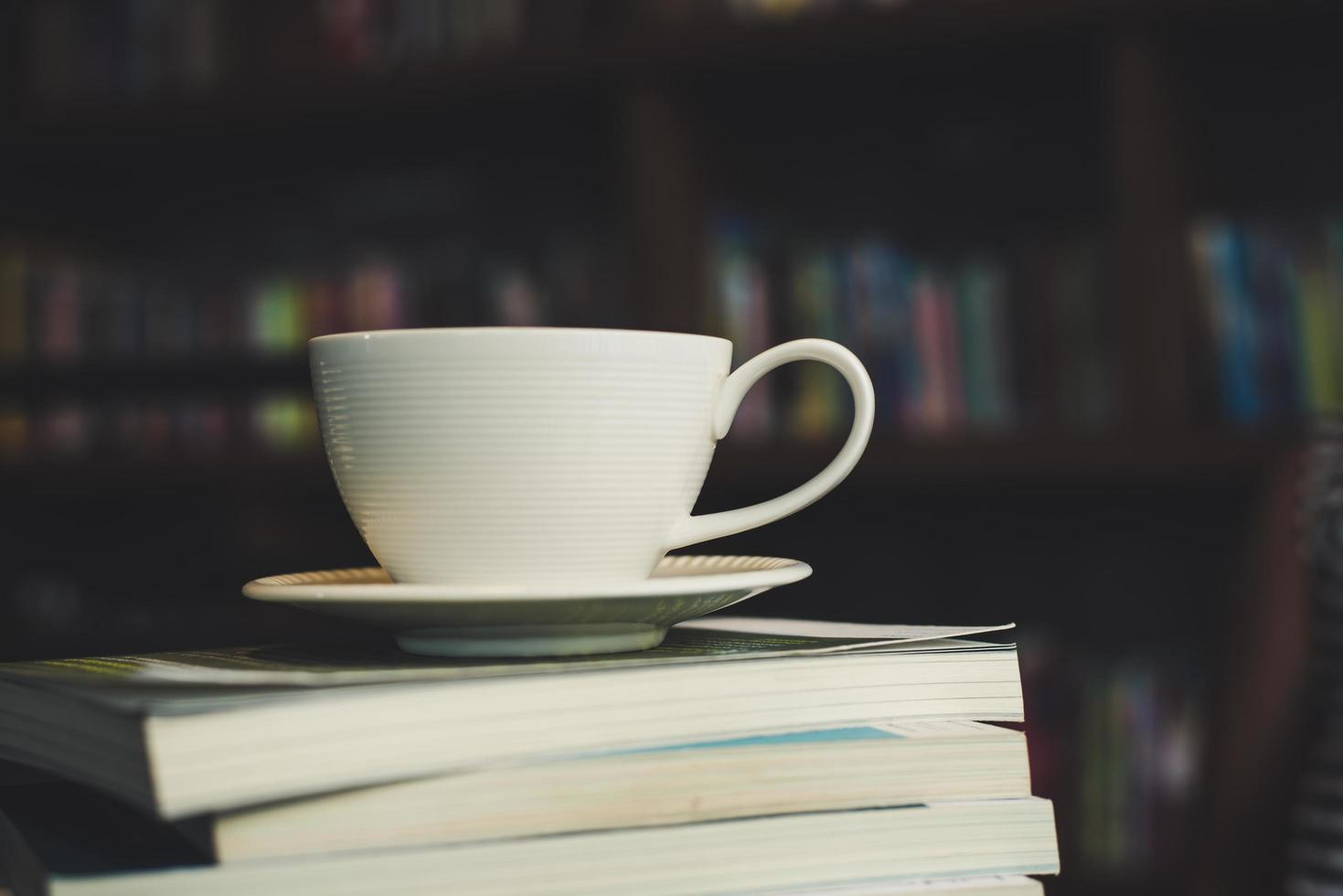 Coffee cup and stack of books on wood table photo