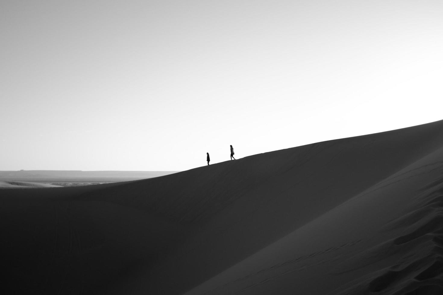 Silhouette of two people walking on desert ridge photo