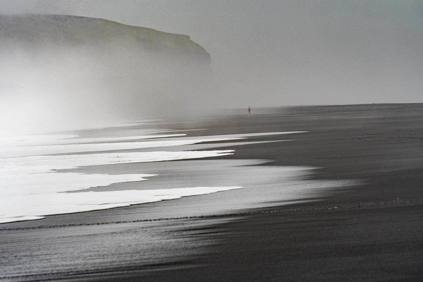 Black beach shore with fog photo