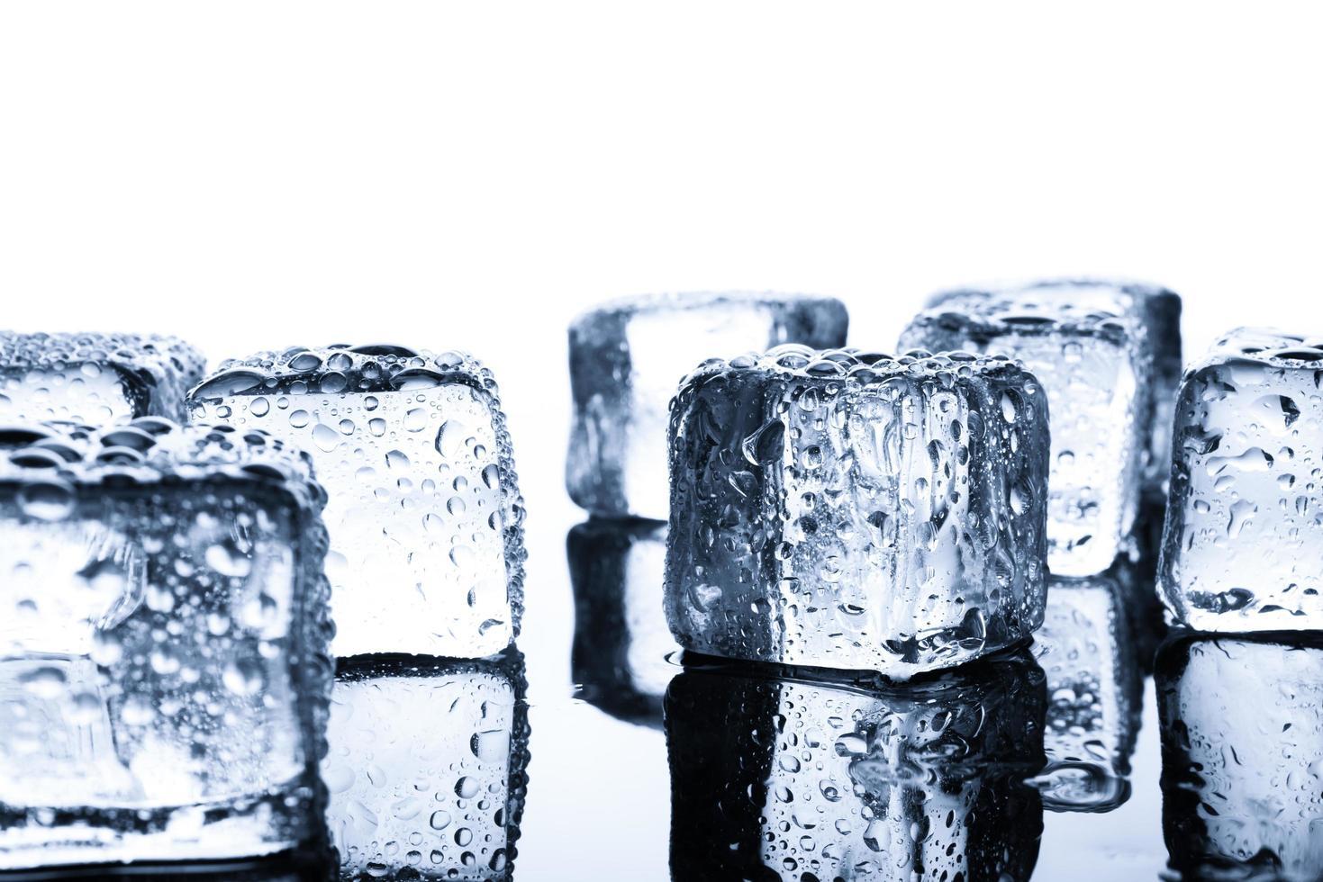 Close-up de cubitos de hielo húmedo sobre fondo mínimo foto