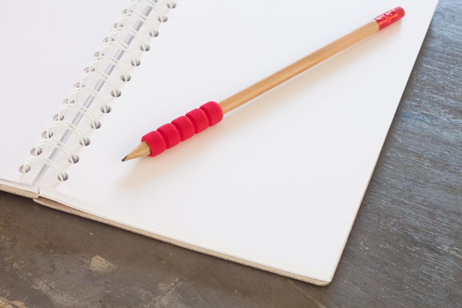 Cuaderno en blanco con lápiz sobre un fondo gris foto