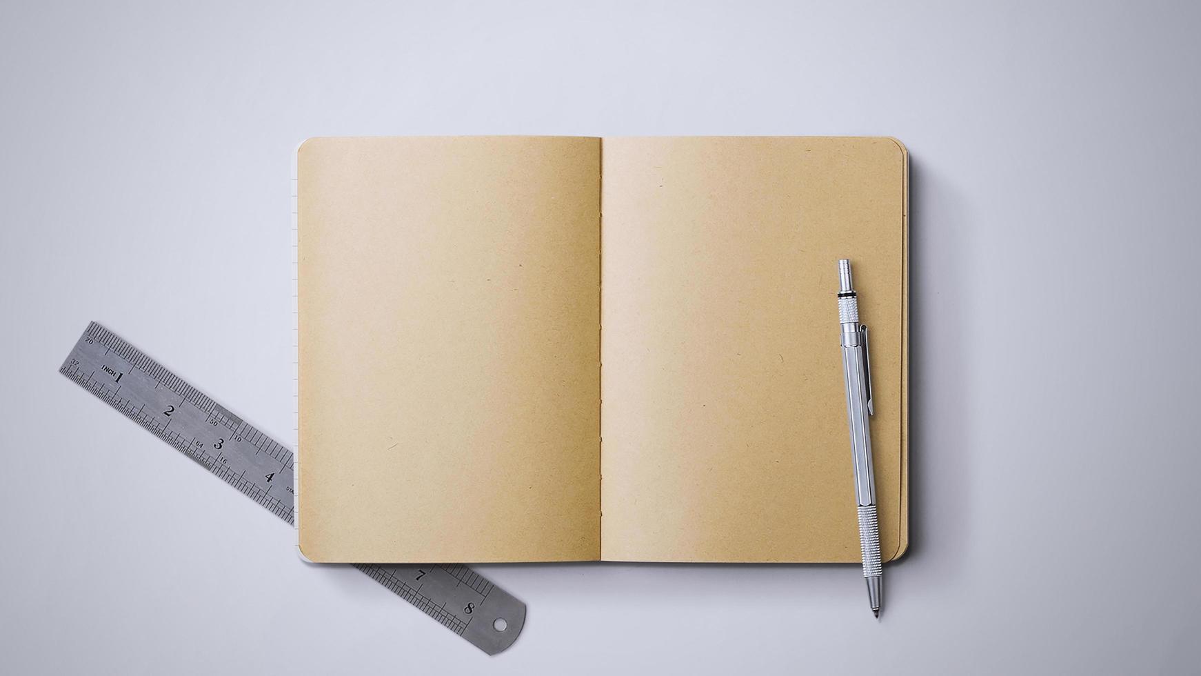 cuaderno con bolígrafo y regla foto