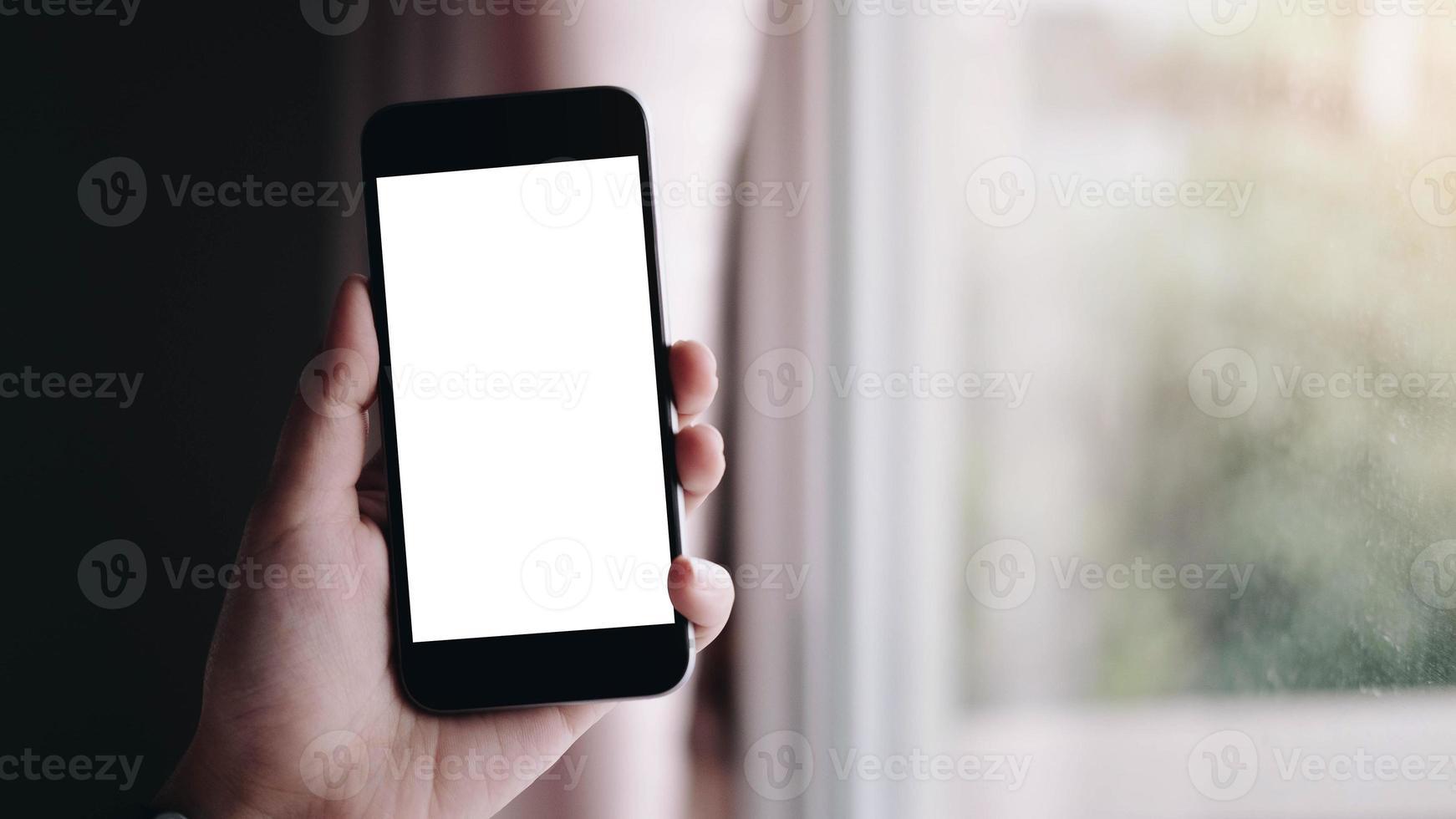 Primer plano de la mano de una mujer con un teléfono inteligente con pantalla en blanco en casa foto