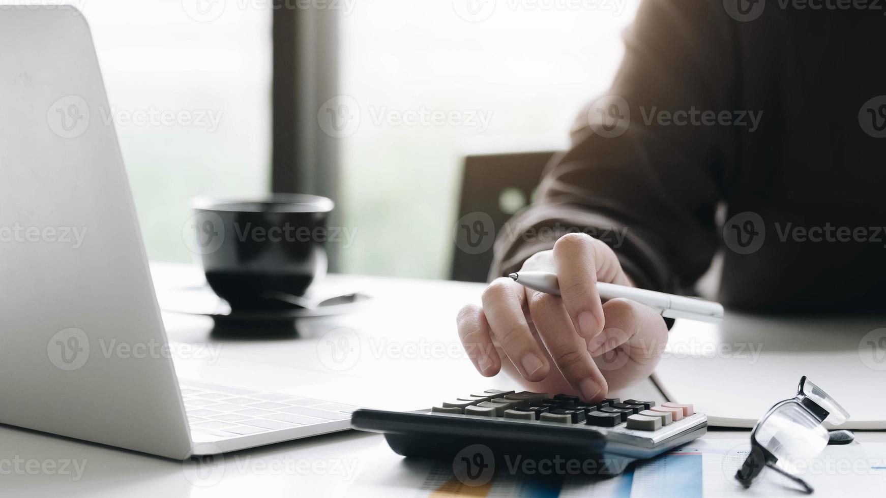 mujer de negocios, utilizar, calculadora, y, computadora portátil, en, escritorio de oficina foto