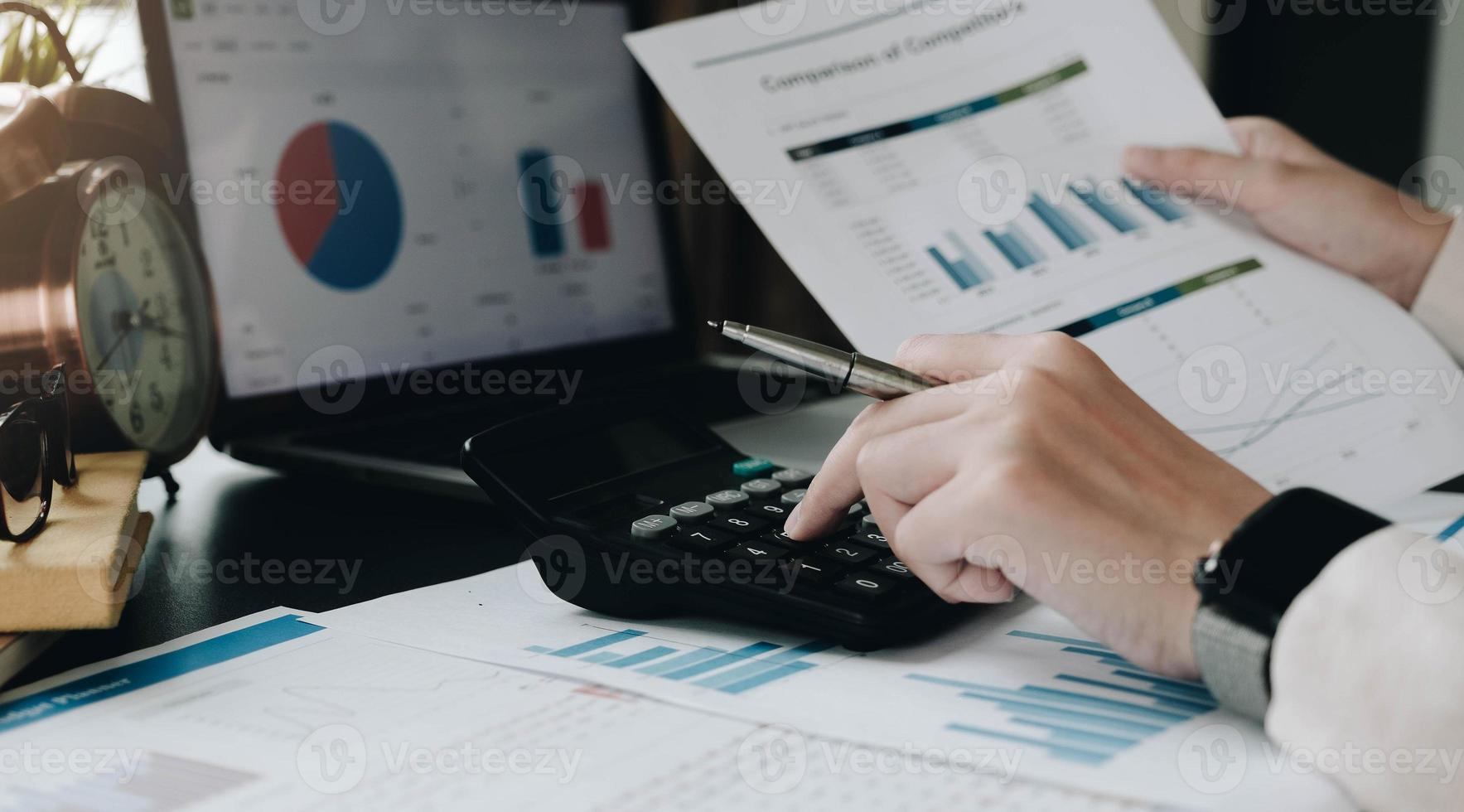 Business woman using calculator and laptop at office desk photo