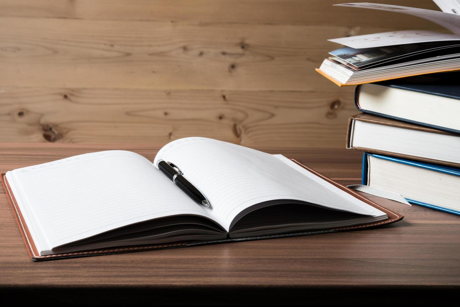 Stack of open books on a wooden table photo