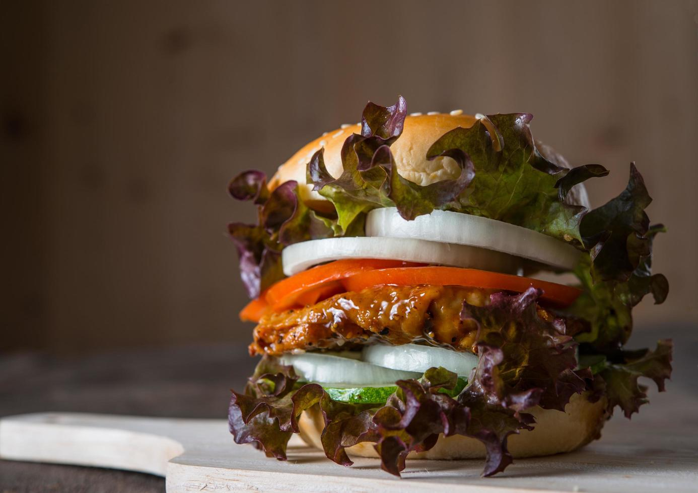 Homemade chicken burger with lettuce, tomato and onion photo
