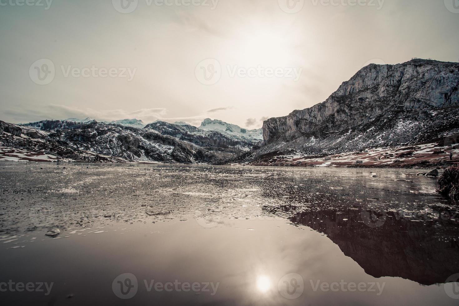 Mountain range reflecting in a frozen lake photo