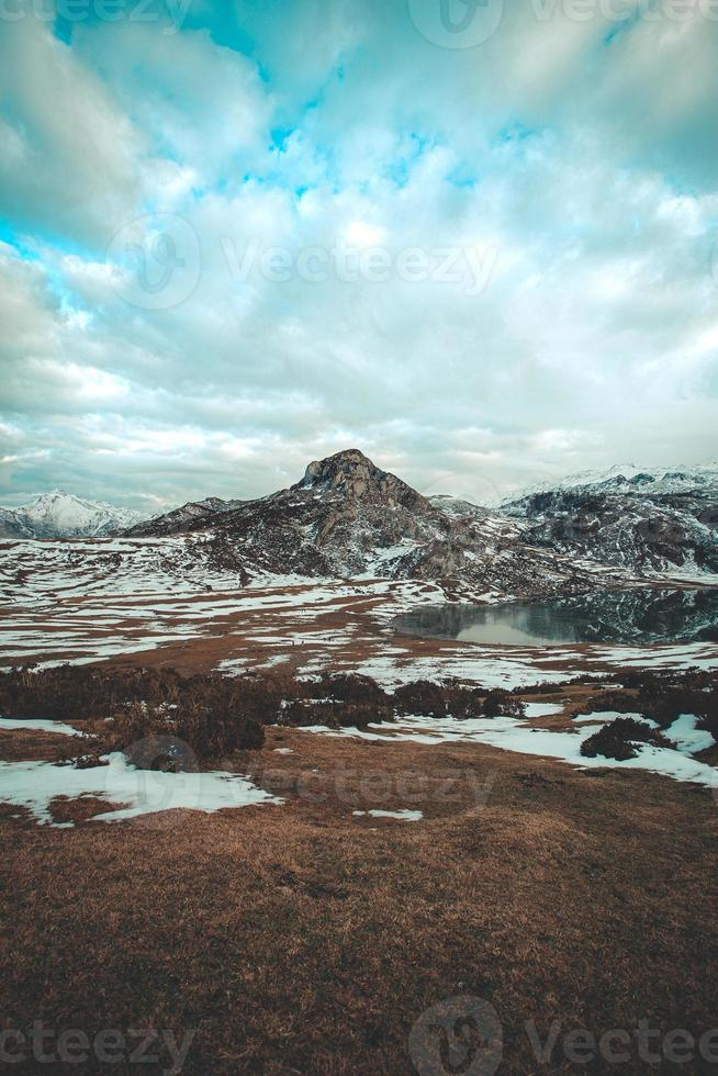 Wide angle shot of a frozen lake in front of a snowed mountain photo