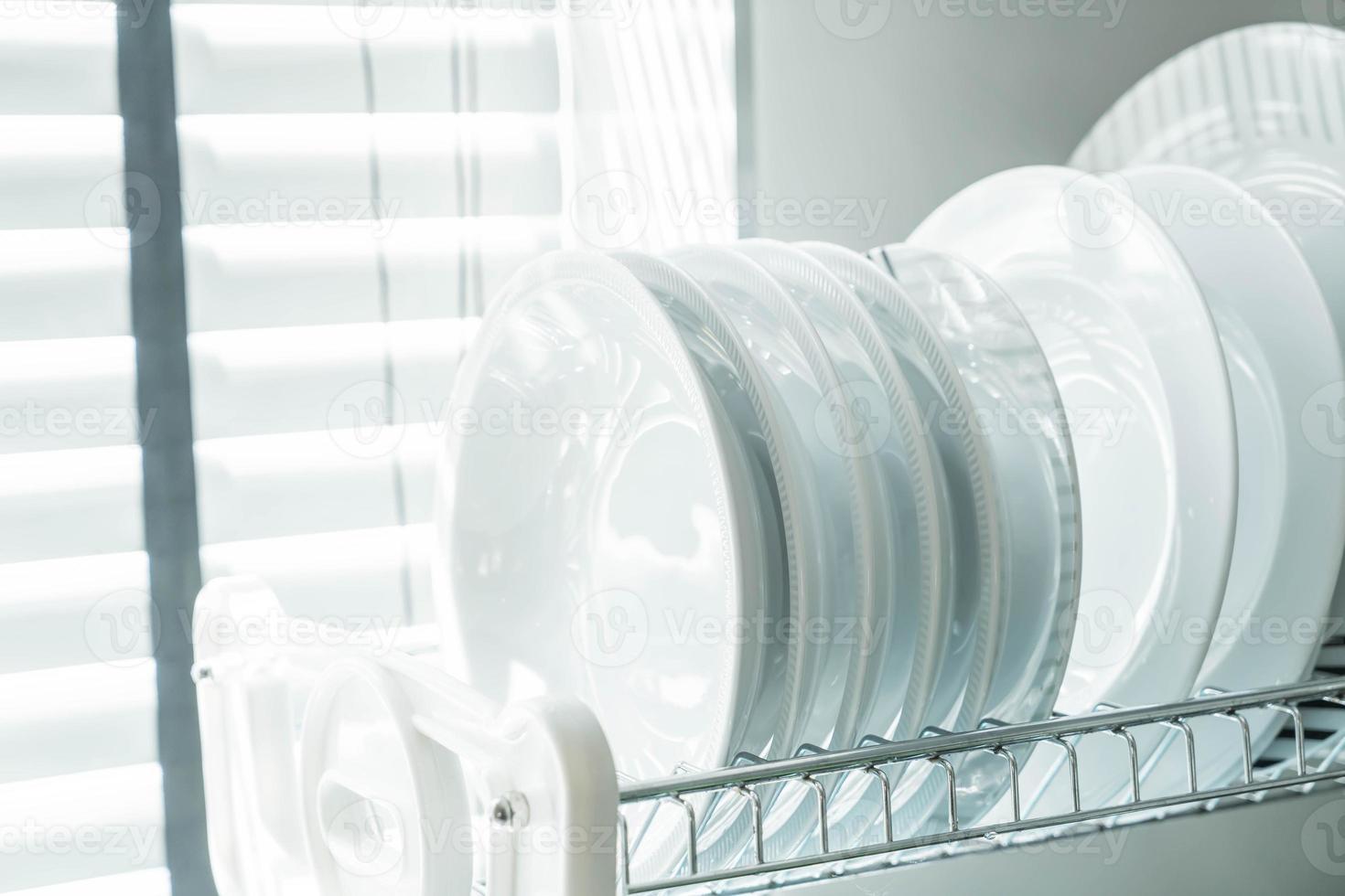 platos blancos limpios en un estante para platos foto