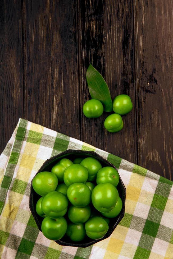 Ciruelas verdes ácidas en un recipiente sobre una servilleta a cuadros sobre un fondo de madera oscura. foto