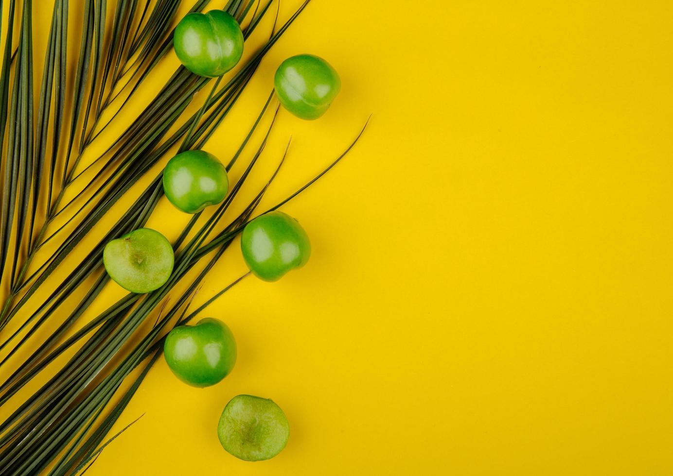 Top view of sour green plums with a palm leaf on a yellow background photo