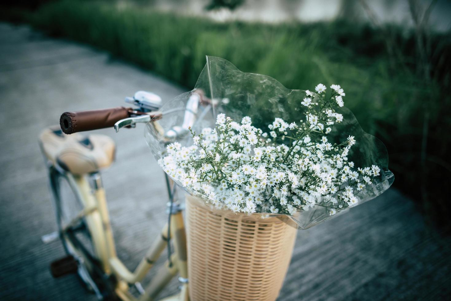 Vintage bicycle with a basket full of wild flowers photo
