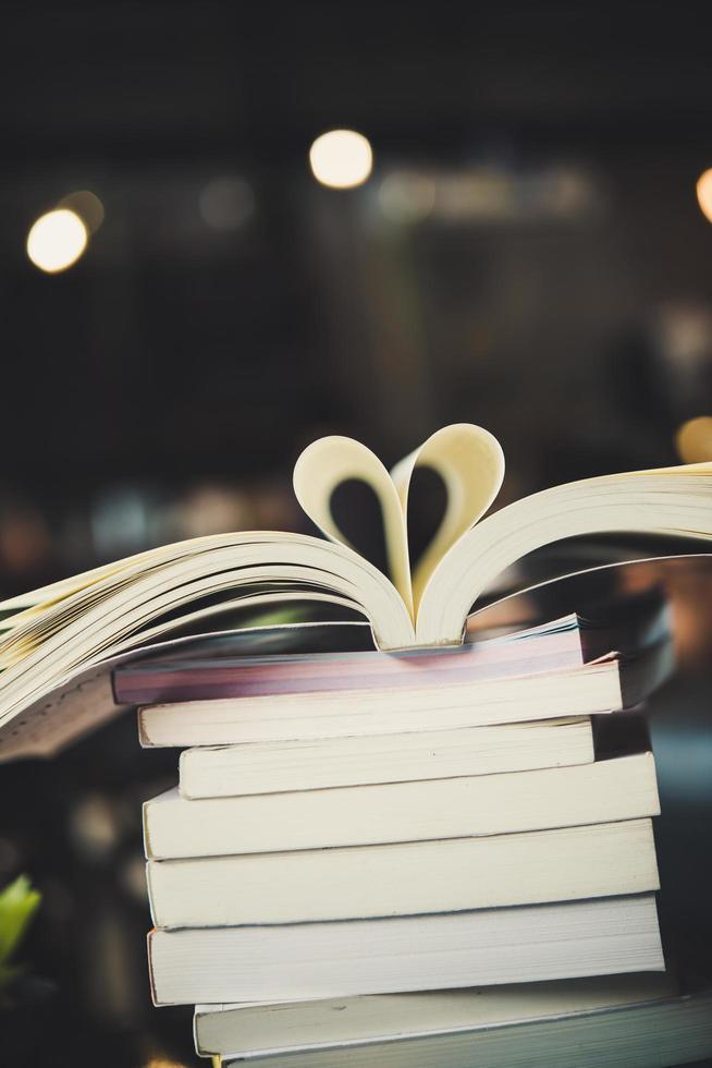 Montones de libros sobre una mesa sobre un fondo de biblioteca borrosa foto