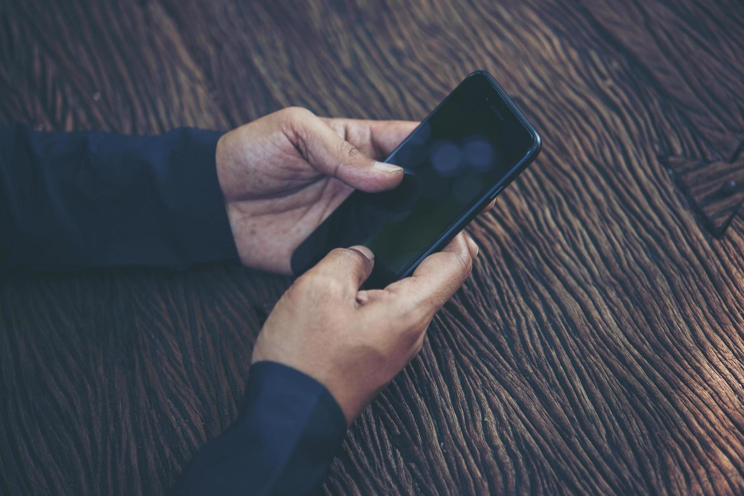Person holding smart phone at a table photo