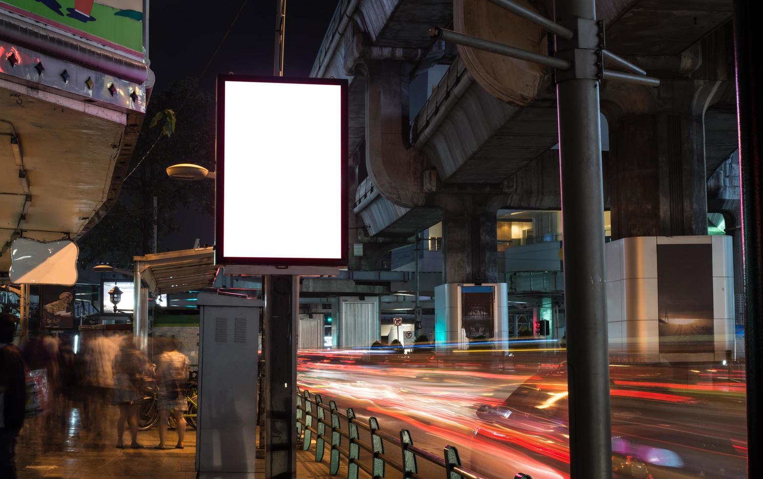 Cartelera en blanco con espacio de copia junto a la carretera por la noche foto