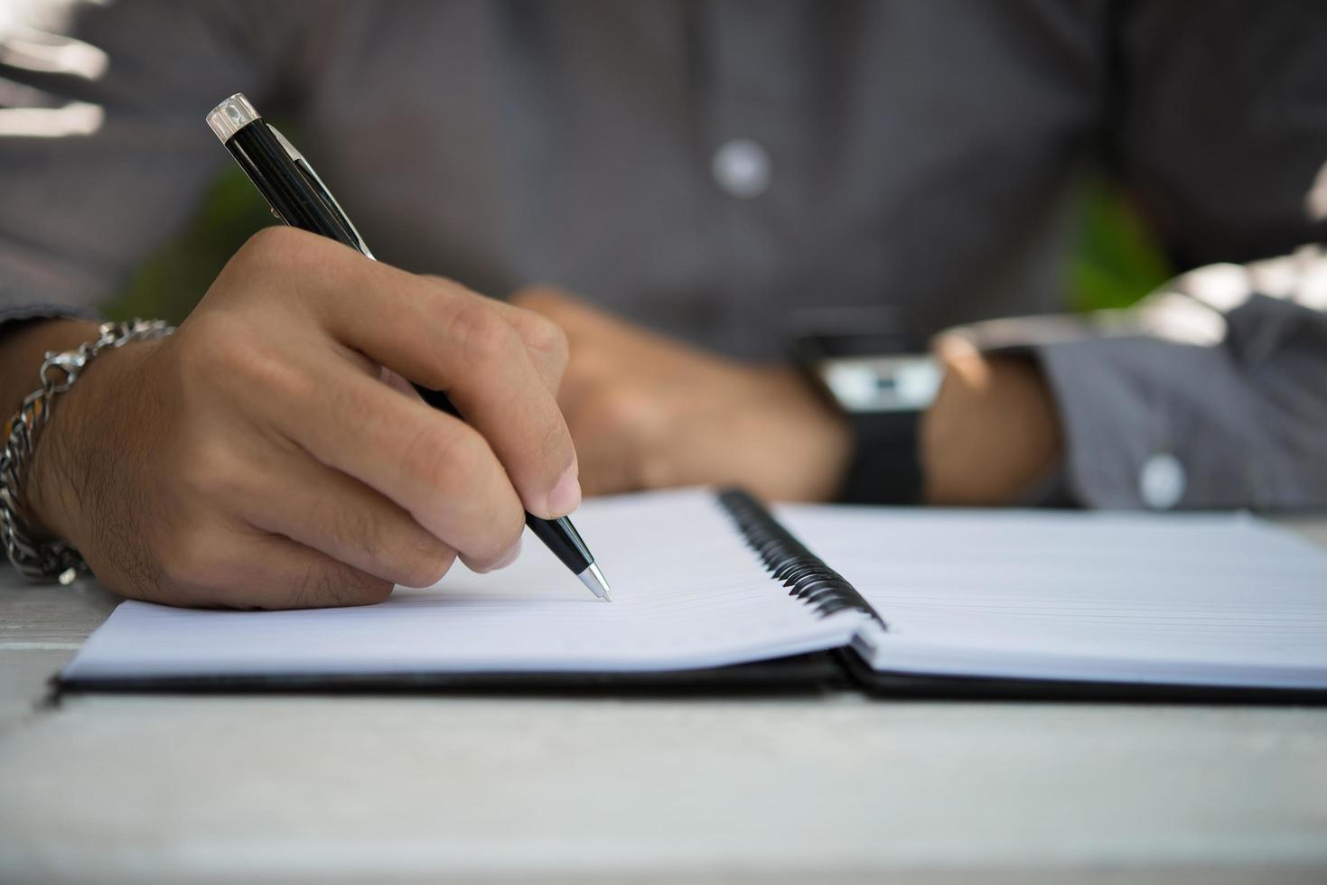 Man writing on notepad while sitting relaxing at home garden photo