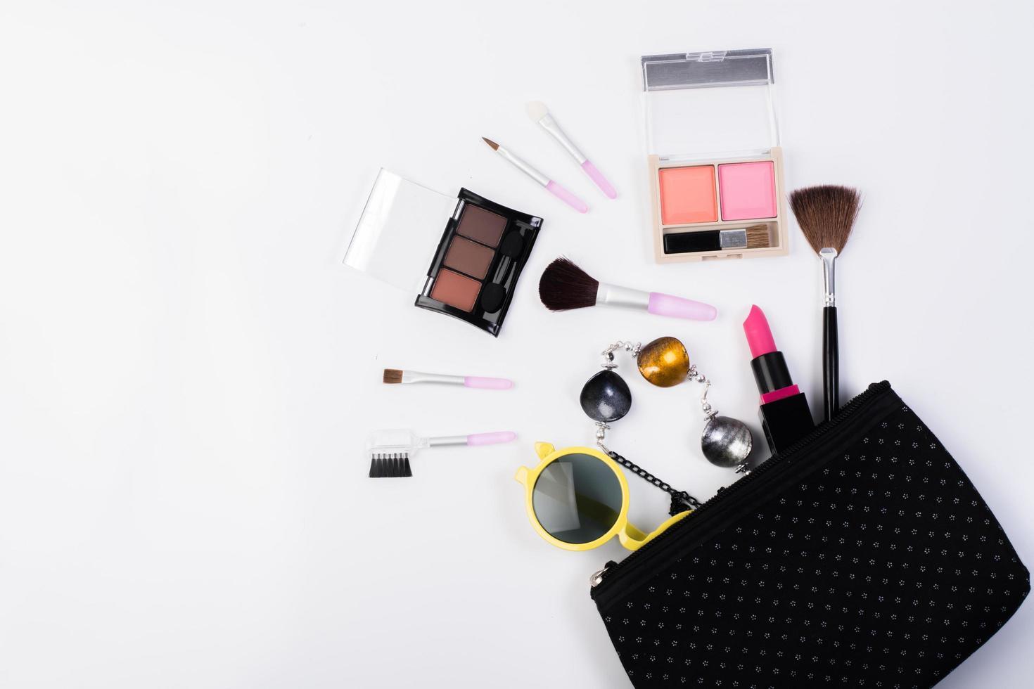 Vista superior de una bolsa de maquillaje con productos de belleza. foto