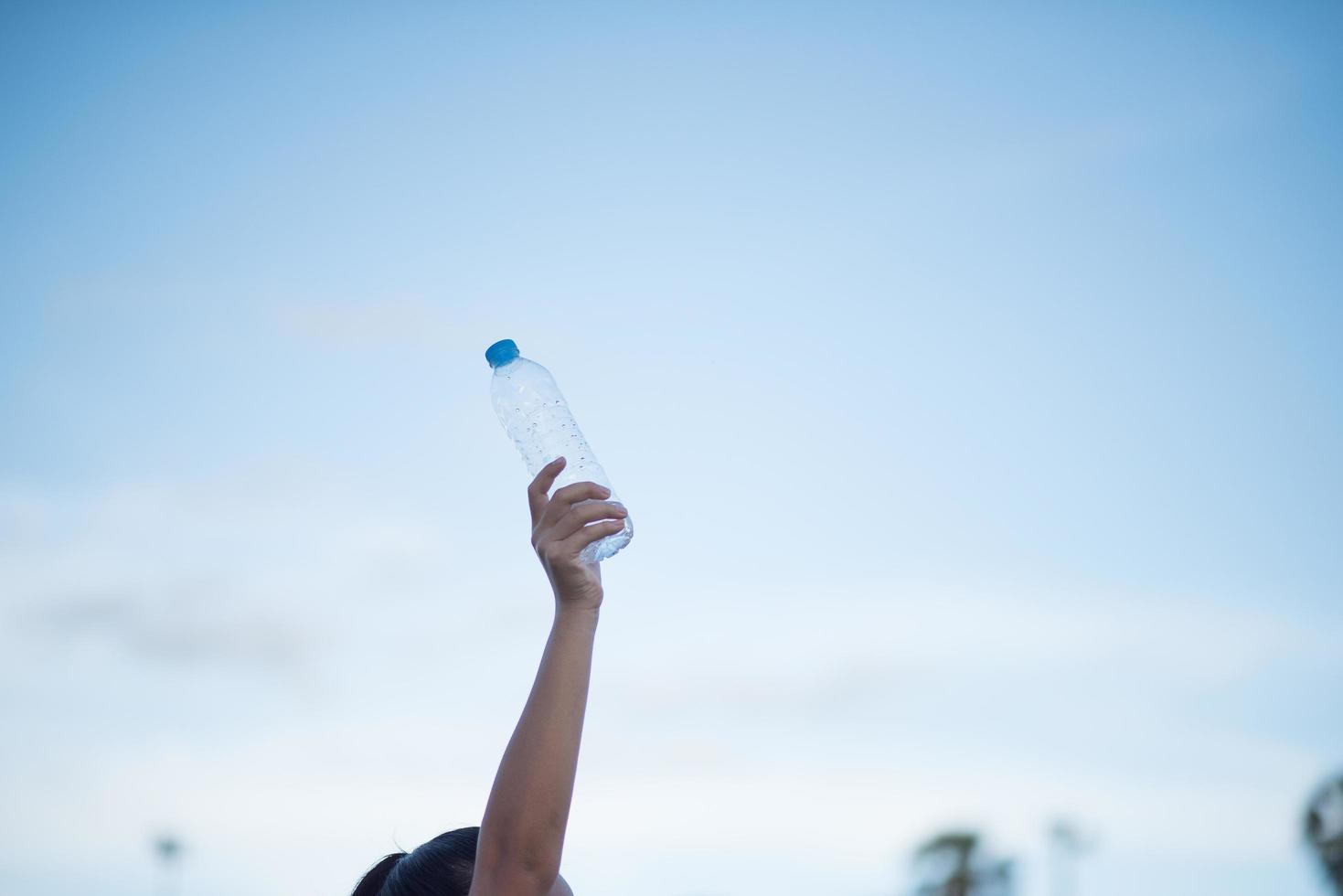 mano de mujer sosteniendo una botella de agua de plástico foto