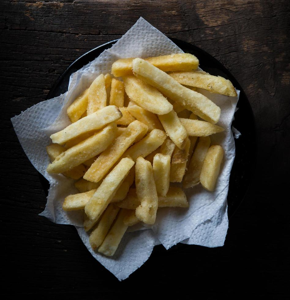 Tasty french fries on wooden table background photo