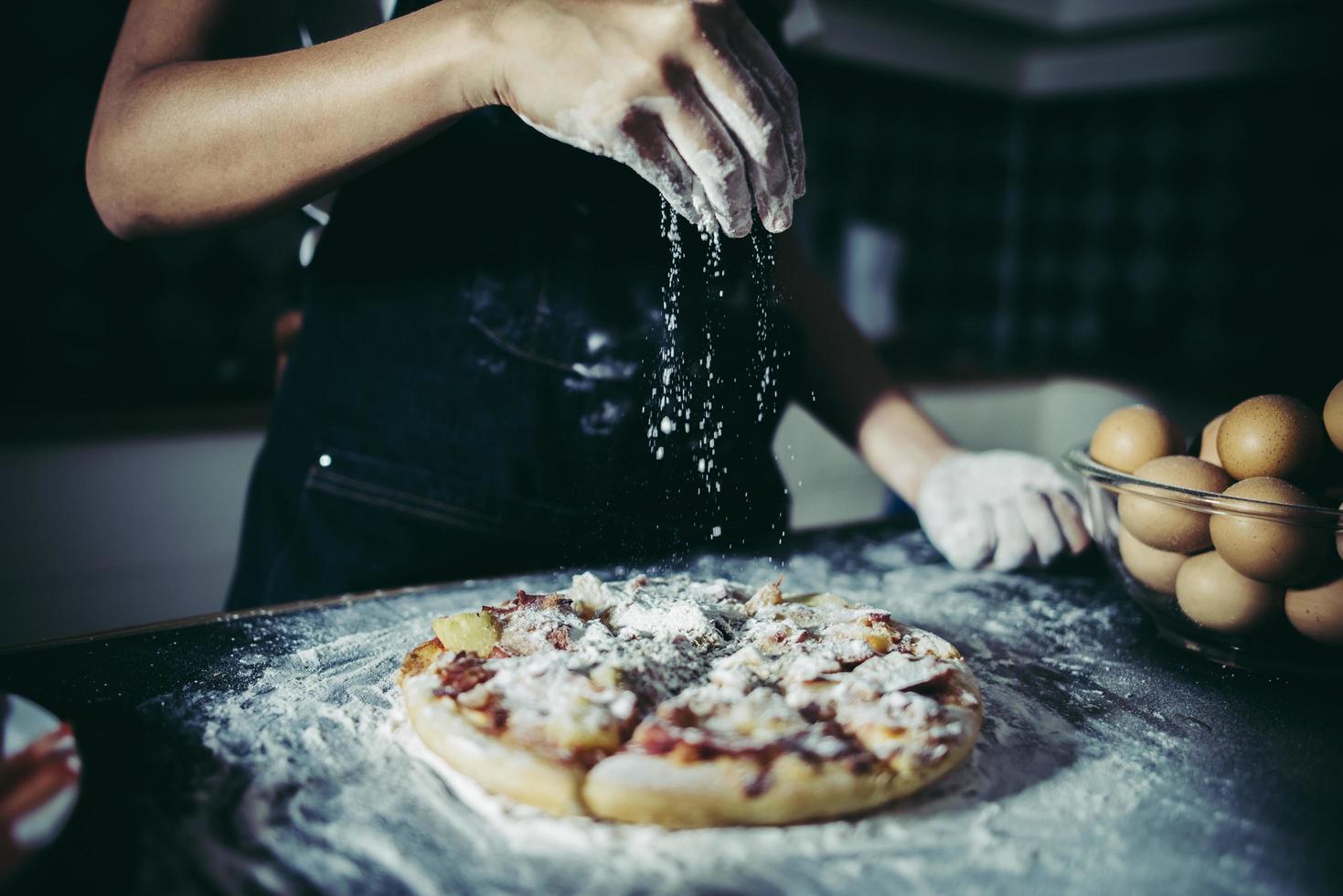 Manos del chef vertiendo harina sobre masa cruda foto
